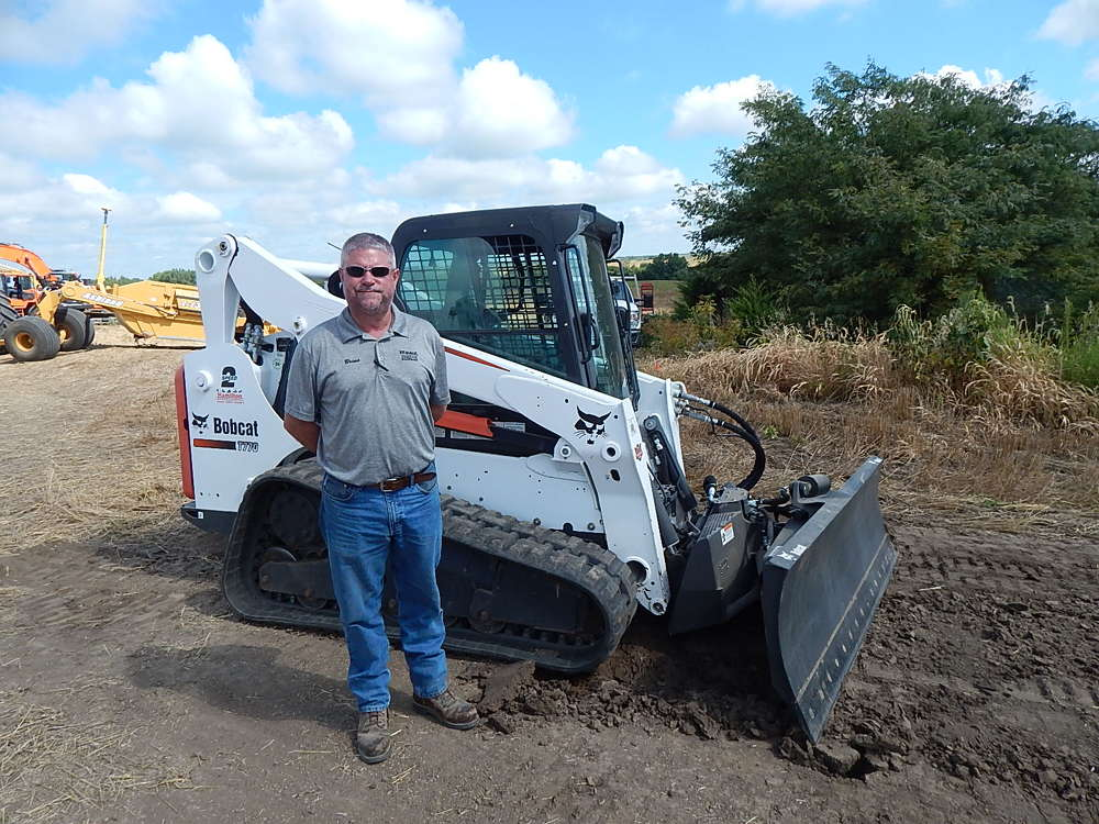Brian Motschenbacher, sales manager of Hamilton Equipment Co., Lincoln, Neb., stands with a new Bobcat T770.