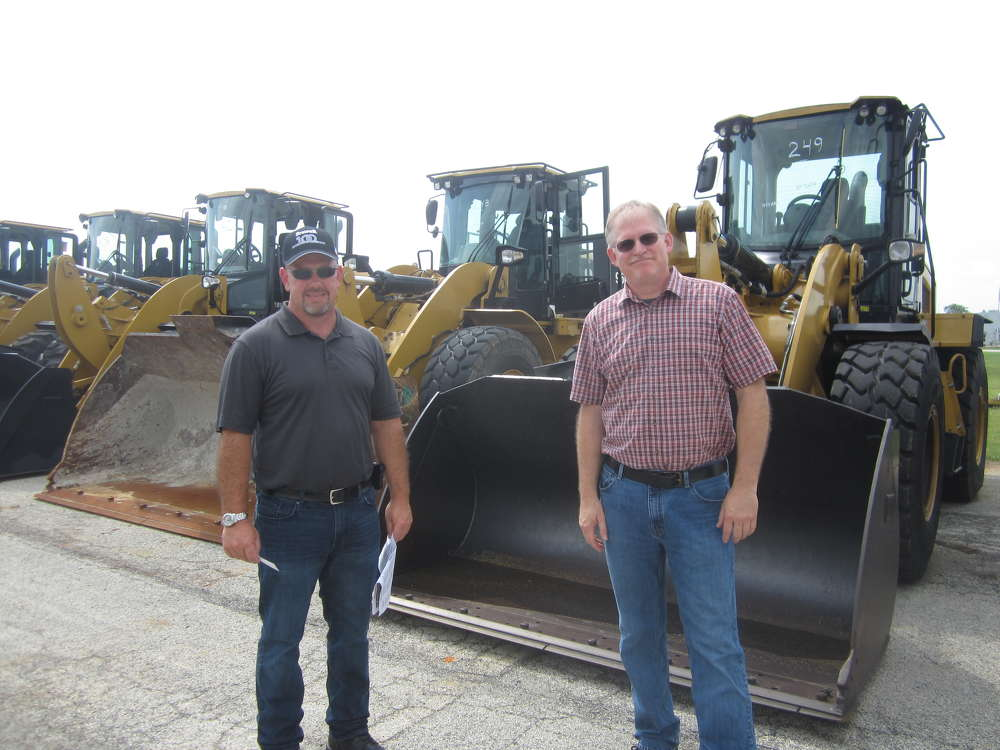 Dave White (L) and Mark Freudinger, both of Quantum Technical, look over the Cat wheel loaders at the sale.