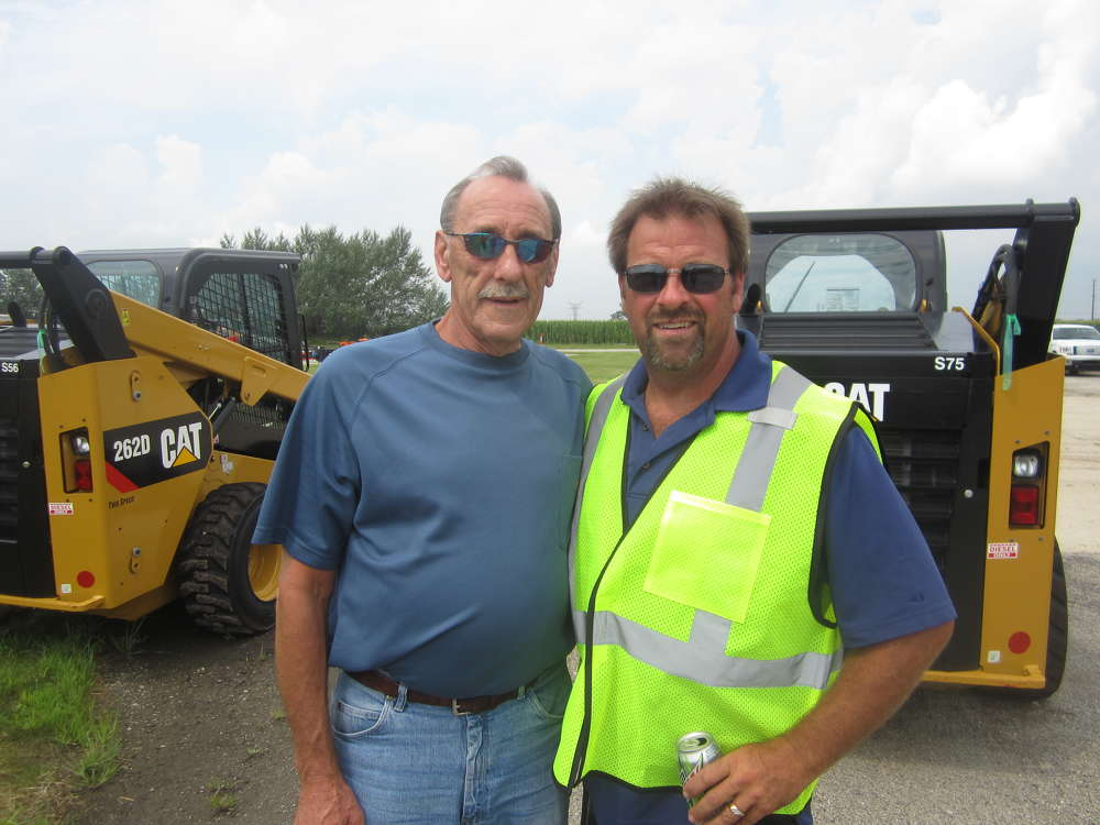 John Einoder (L), owner of J T Einoder Inc., and John Starek, operations manager of Arctic Snow & Ice Control products, discuss the skid steers.