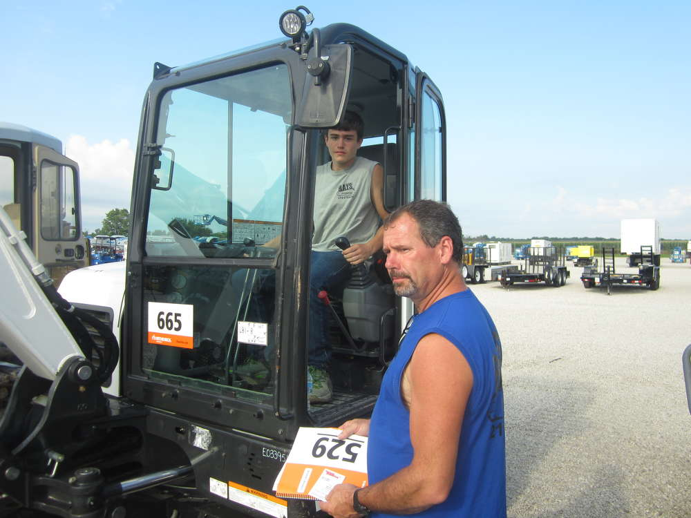 Ray Selke (R), owner of Rays Excavating, and his son, Devin, inspect this Bobcat compact excavator.