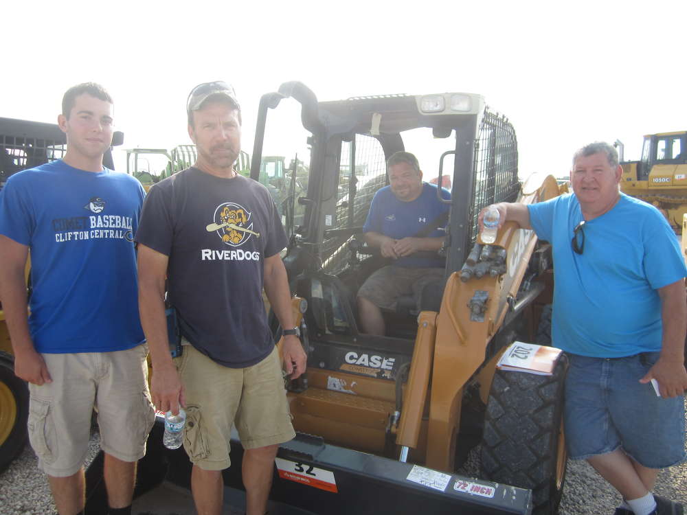 (L-R): Dave and Tony Zell, Basil Hicks and Ray Cantore gather around this Case SV 300 skid steer that they just purchased.