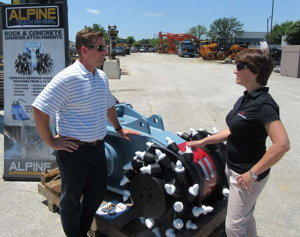 Cathy DeSanto (R), Alpine Sales & Rental Corporation's operations manager, talks with Tate Begley of Rudd Equipment Company sales representative at the event.
