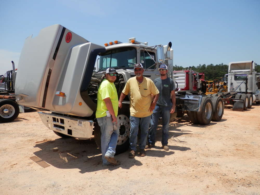 (L-R): Perane Mayo, Corey Tucker and Landon Mayo consider bidding on this 1999 Mack RD688s T/A truck tractor.