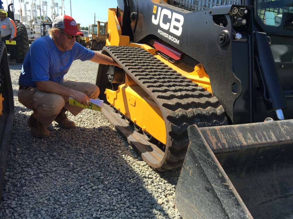 David Eastman, GLM Company in Travelers Rest, S.C., looks at JCB compact track loaders, grinders and  a dump truck during the sale.