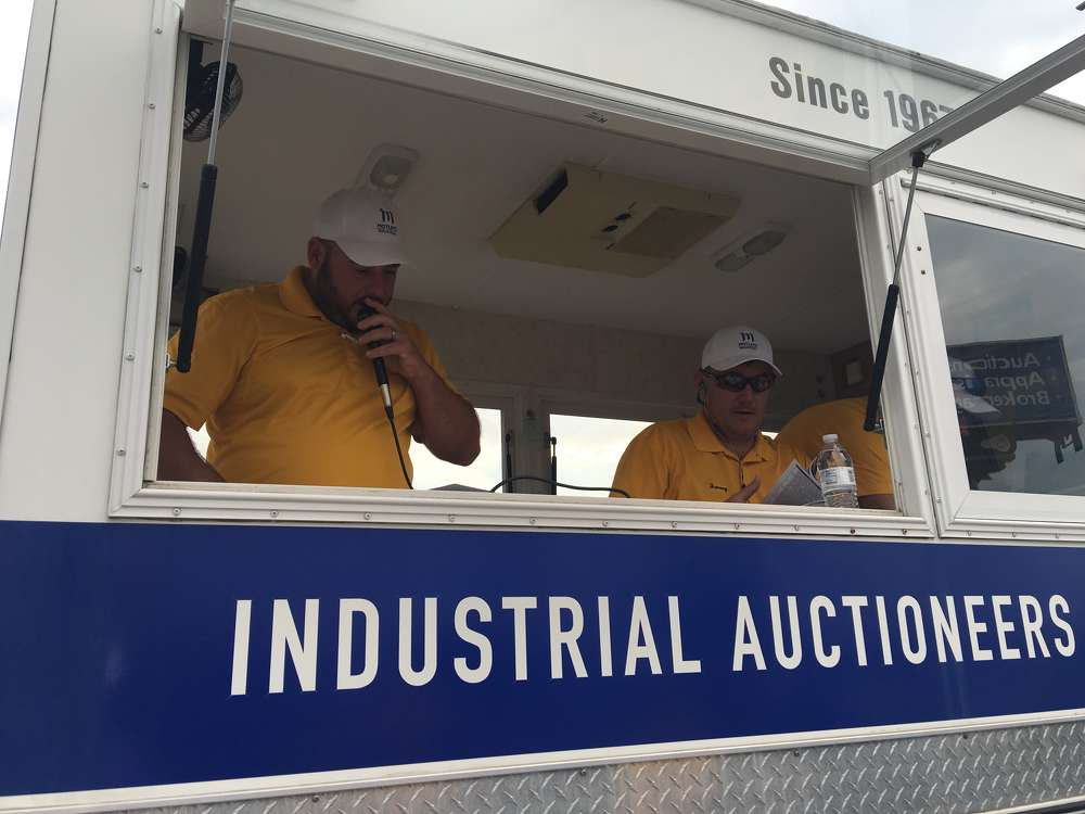 Jeremy Hooks (L) and Jeremy Lehman, both of Motleys Industrial, read over announcements before the start of the sale.