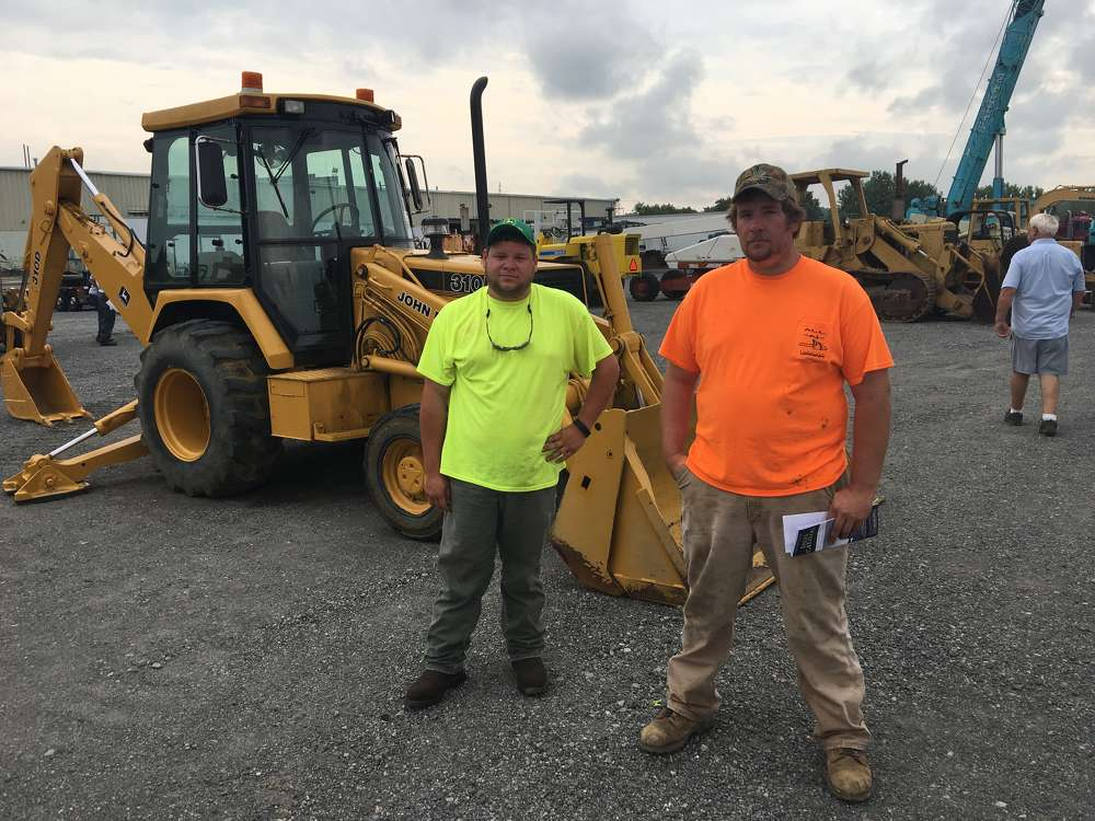 Blake Toombs (L) and Andrew Barton, both of All-N-Logging in Drakes Branch, Va., show interest in this John Deere 310 backhoe.
