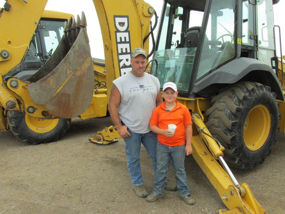 Robert Jones (L) and his son, Owen, of Jones Excavation and Dozing in Tipton, Kan., pose with their latest purchase from the auction — a John Deere 310 SG loader/backhoe.