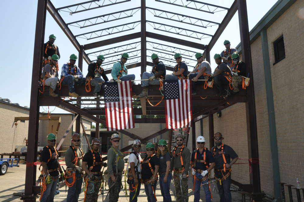 Following ACS's first training class in June, ironworkers (sitting on the steel training tower) are now working on job sites building a high school and community college in Katy and Missouri City, Texas, respectively. Also shown are operational excellence coordinators and ACS staff and instructors.