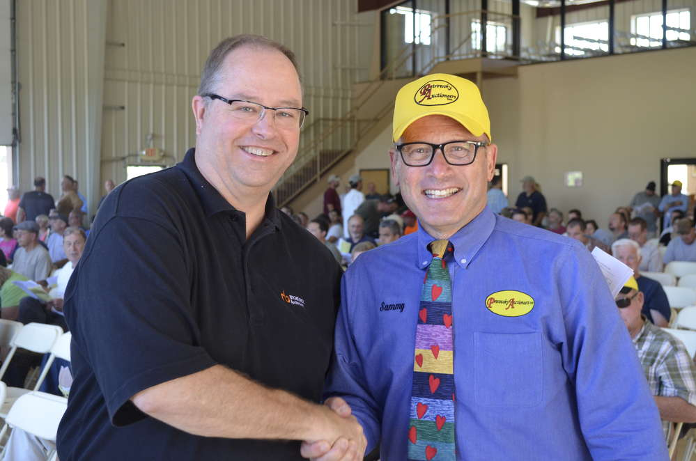 Kevin Kobus (L), Ritchie Bros. Auctioneers vice president of operations of United States and Latin America, congratulates Sam Petrowsky on the sale of his company and looks forward to an exciting future.