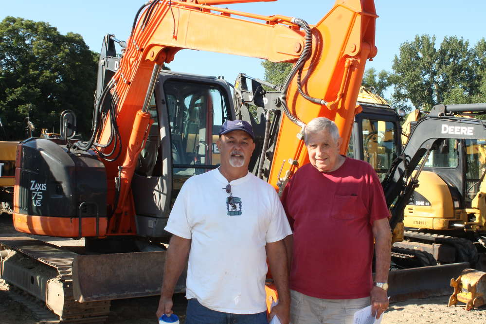 Jim Violett (L), owner of JV's Home Improvement, Elizabeth, Conn., and his father-in-law, Ronald DeCosta, were checking out the Hitachi Zaxis 75 mini-excavator.