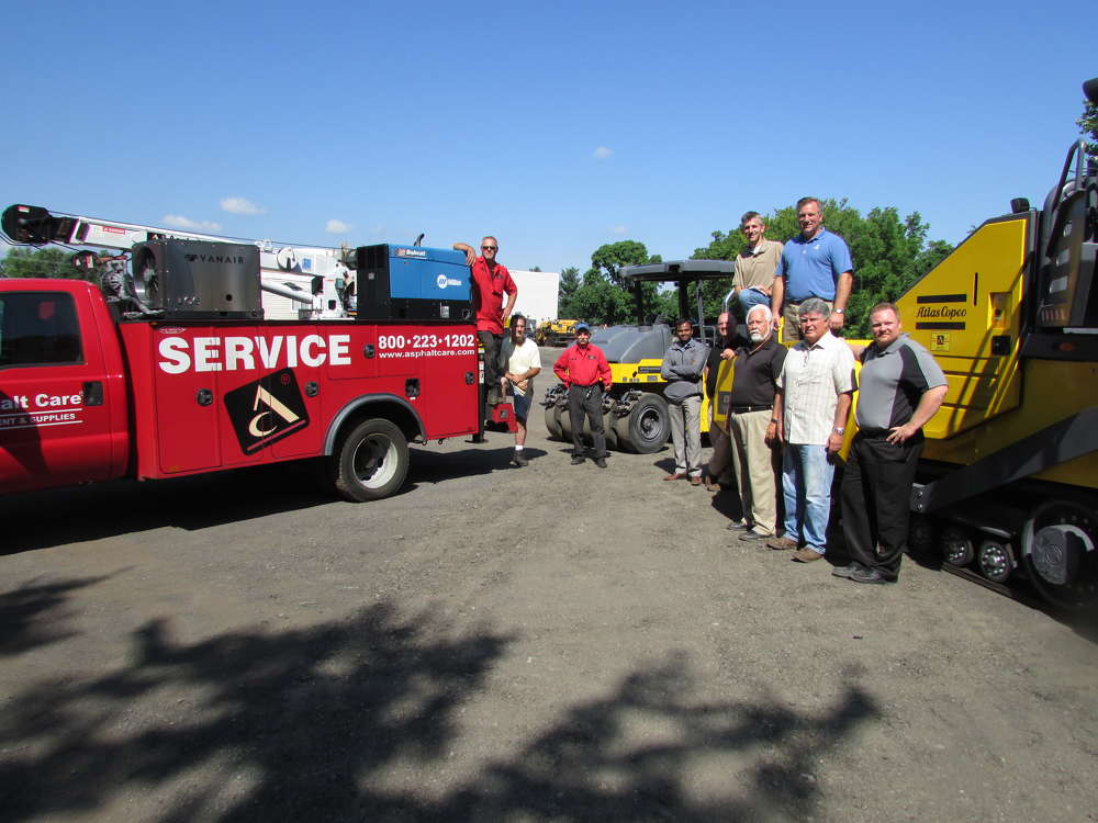Standing in front of an Atlas Copco Dynapac F800T tracked paver and Dynapac CP1200 roller (L-R) are Glenn Silfies, service technician, and Len Metrolo, technician; Andy Andrzejewsky, rental operations, all of Asphalt Care Equipment; Vijay Palanisamy, product manager-pavers, and Brian Henk, regional sales manager, both of Atlas Copco; Dan and David Fackler (on top of paver), both of Asphalt Care Equipment; and Tony Stoecker, sales representative; Jim Hannon, sales representative; and Bill Jainnin