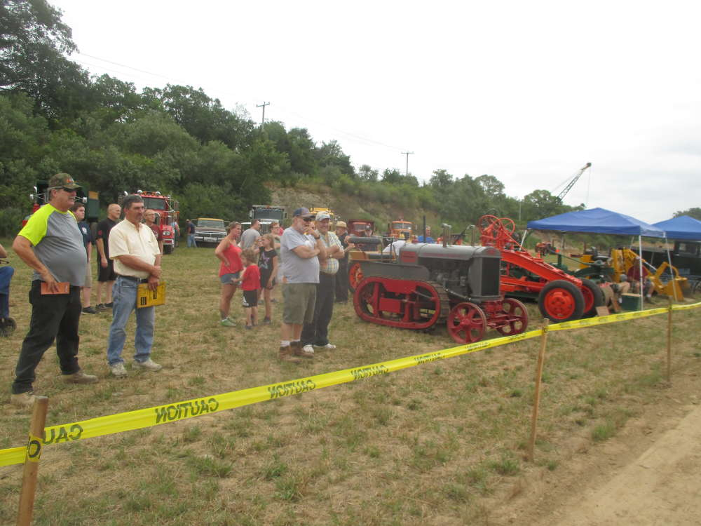 Spectators, including many families, stand along the ropes watching a demonstration in the fields of Mark Gluck's Farm as antique equipment still hums.