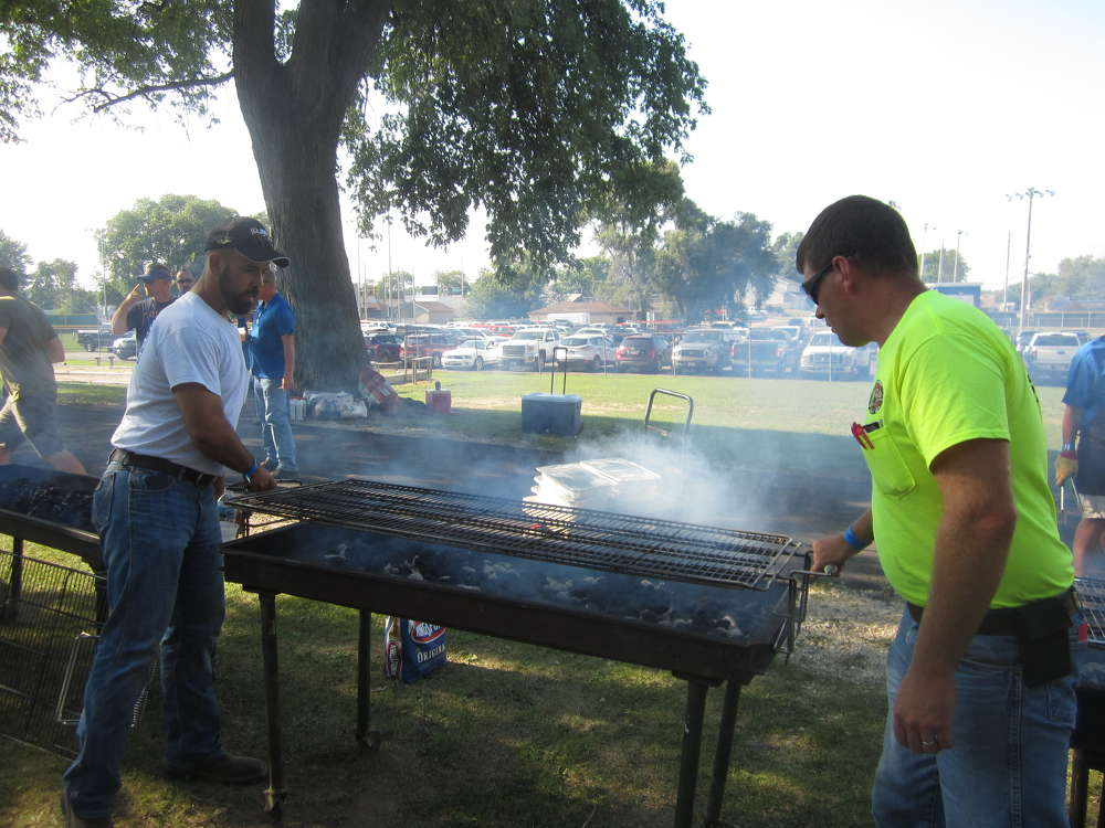 Adam Salinas (L) and Nick Stipanovich, both of Illinois Truck & Equipment, prepare the grills for the annual steak fry.