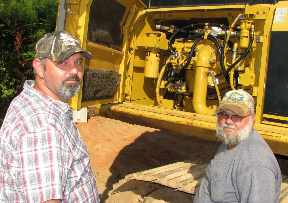 Tim Thompson (L) and John Short, both of Thompson Grading & Clearing, Bowden, Ga., begin their inspection of this Cat 345 BL excavator.