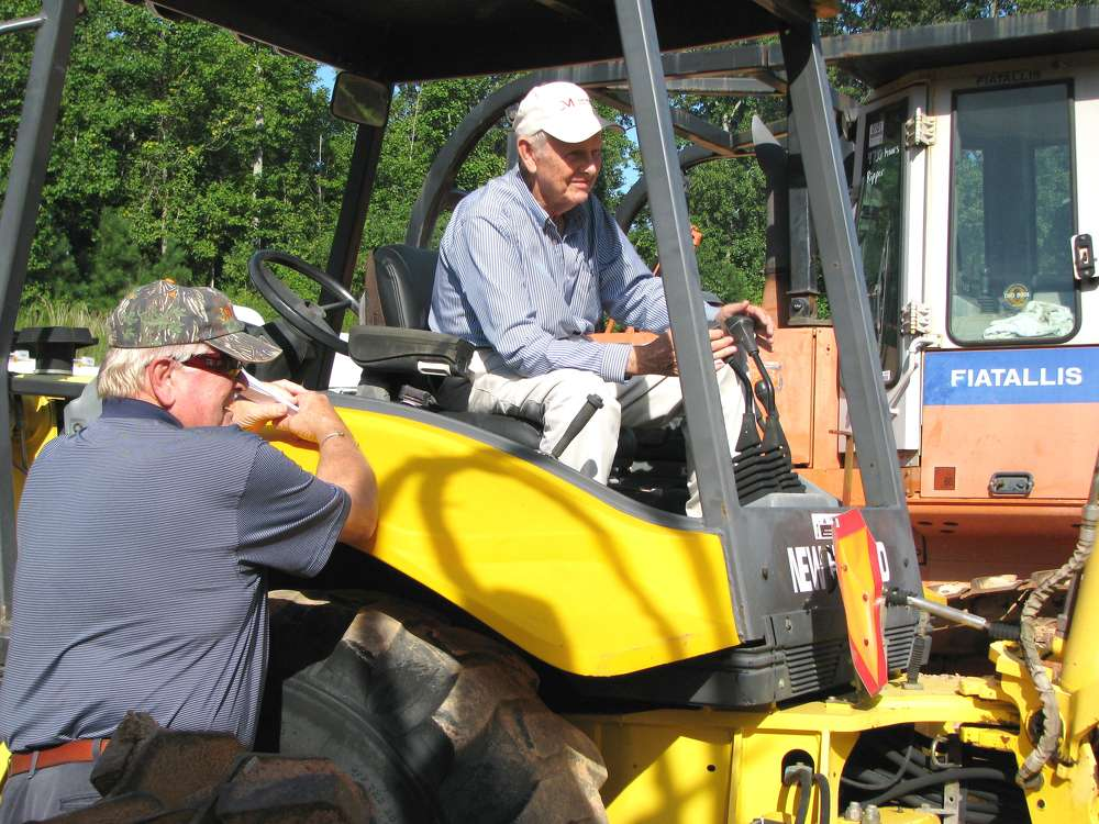 Jimmy Gray (L) and James Short of James Short Tractors & Equipment, Carnesville, Ga., test a  New Holland backhoe loader.