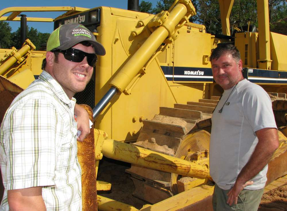 Caleb Phillips (L), Granite Mountain Machinery, Conyers, Ga., and Don McCullers, Wright Pipe & Grading, Loganville, Ga., check out a Komatsu dozer.