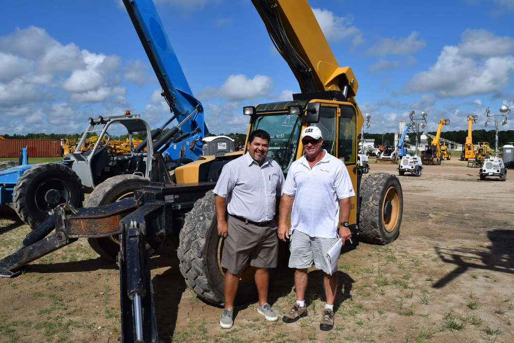 Antonio Ortiz (L) and Mike Reynolds, both of Ring Power, check out a few of the Cat machines at the auction.