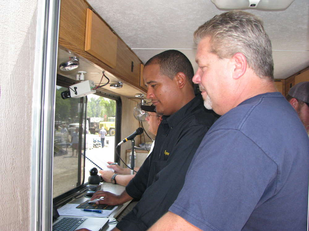 Joseph Pelaez (L) and Larry Garafola of Equipmentfacts, Flemington, N.J., monitor the online bidding from the auction truck.