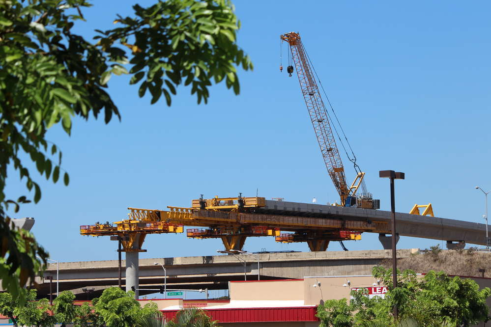 Honolulu Transit photo. Using a crane on top of the guideway for segment erection helps to minimize traffic impacts along Fort Weaver Road.