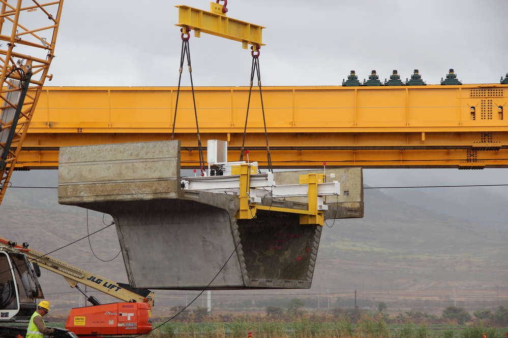 Honolulu Transit photo. The first guideway segment for the Honolulu rail project is lifted onto the steel trusses.