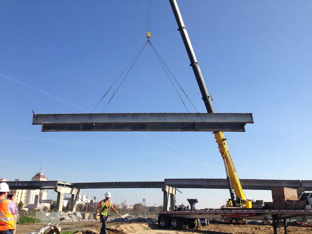 The placement of these girders signifies the midway point of the construction for the bridge.