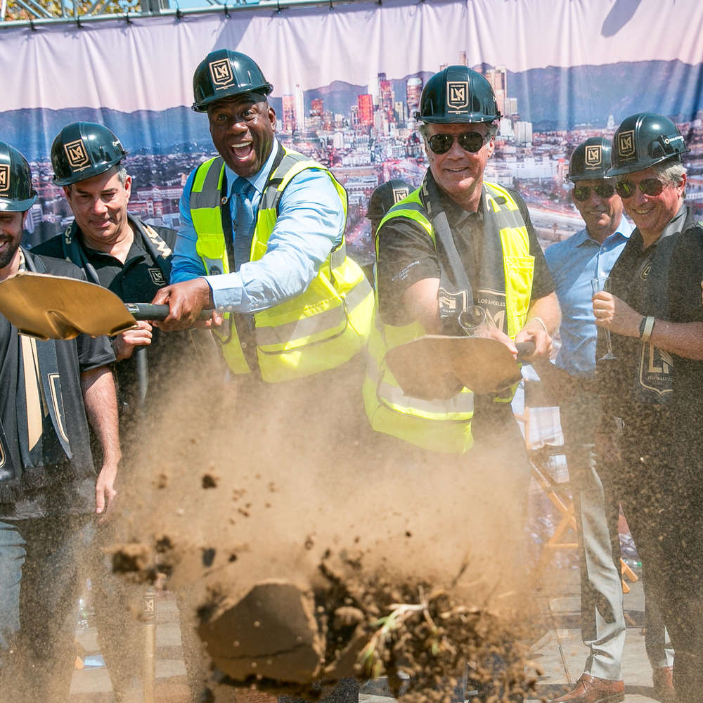 Magic Johnson (L) and Will Ferrell pitch in at the groundbreaking ceremony.