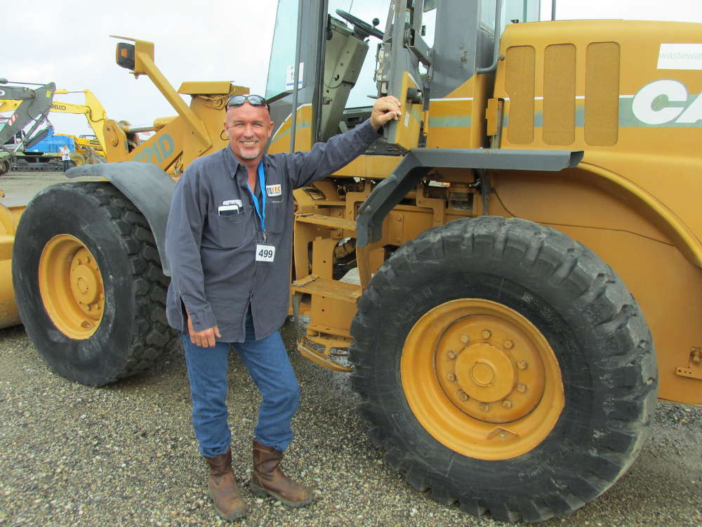 Neil Martin of TEC Well Service in Longview, Texas, gives this 521D Case loader a thorough once-over before bidding on it.