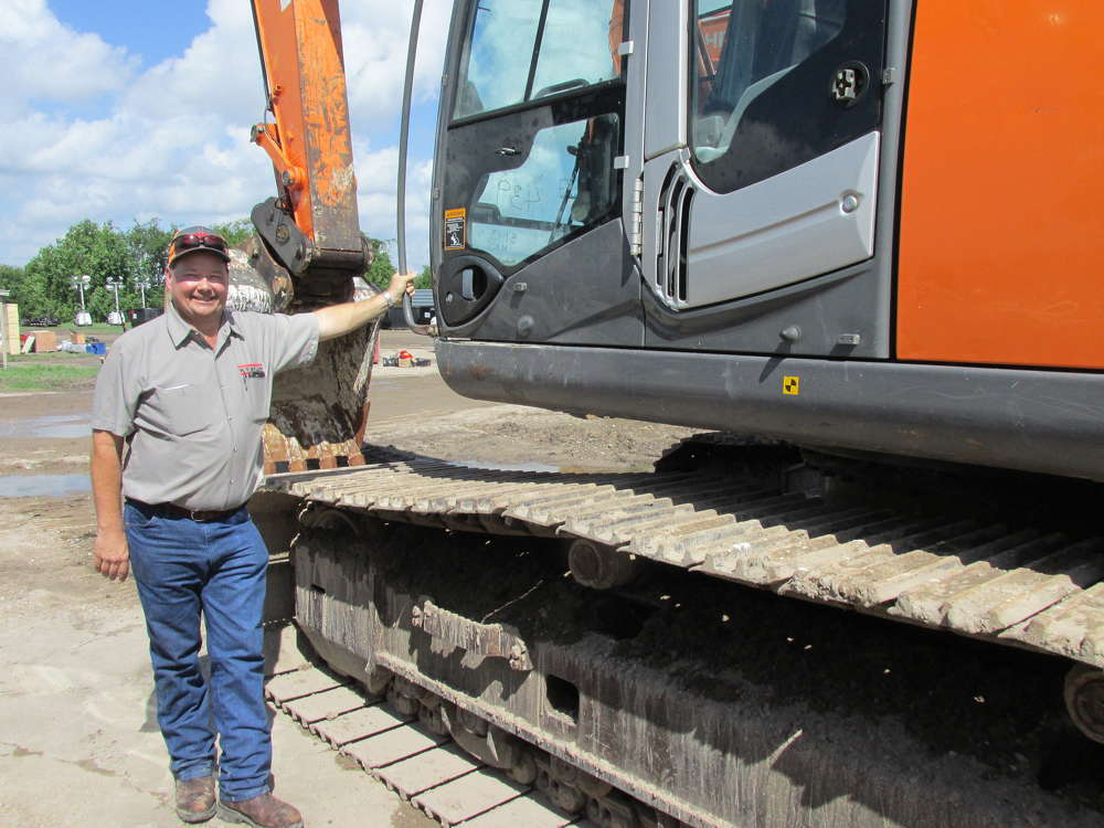 David Smith of W.T. Byler in Houston, Texas, takes a more than curious look at this Hitachi 350 LC excavator.