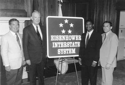 The road sign for the Dwight D. Eisenhower National System of Interstate and Defense Highways, designed by FHWA and the American Association of State Highway and Transportation Officials, was unveiled in a ceremony on Capitol Hill on 7/29/93. Left to right: Chairman Nick J. Rahall (D-WV) of the House Surface Transportation Subcommittee, John Eisenhower,  Federal Highway Administrator Rodney E. Slater, and Chairman Norman Y. Mineta (D-CA) of the House Committee on Public Works and Transportation.