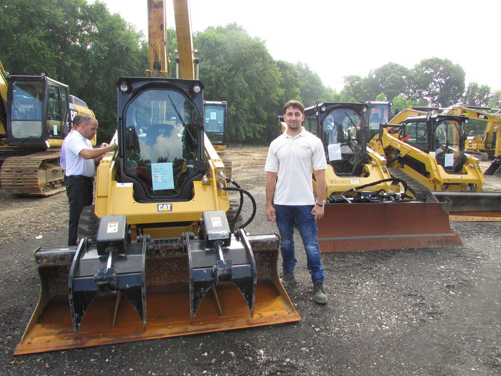 Travis Histed, Color Works Painting Inc., Newcastle, Del., inspects this Cat grapple with 78-in. bucket.