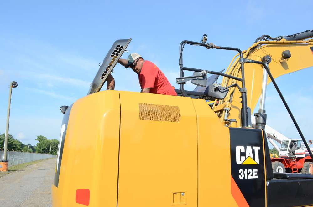Walter Mangual, owner of Mangual Excavations, Philadelphia, Pa., looks under the hood of this Cat 312E hydraulic excavator.