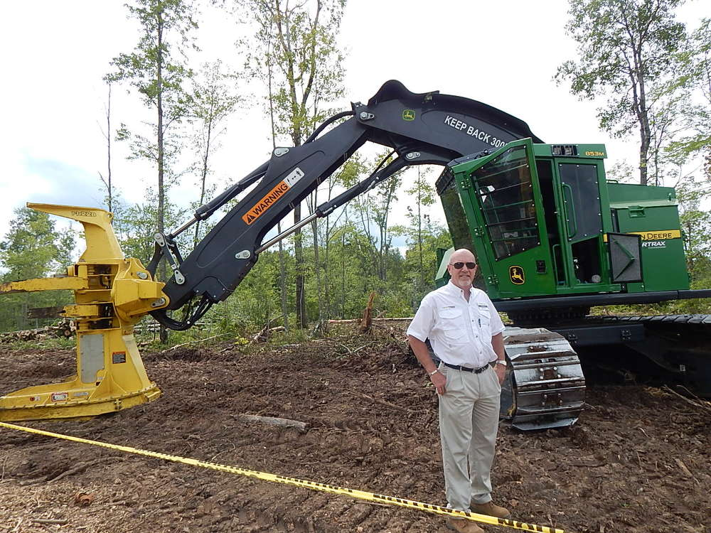 Tim J. Murphy, president and CEO of Nortrax Inc., stands with a John Deere 853M tracked feller buncher.