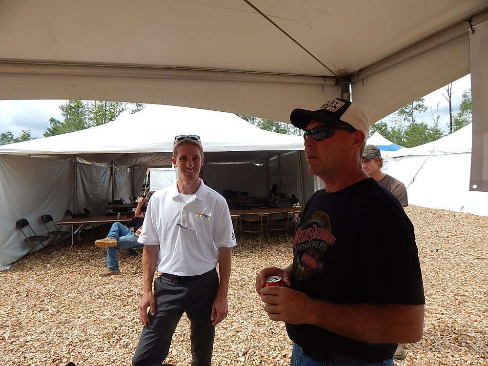 Jacob Kesanen (L), Nortrax product support technology representative, Grand Rapids, Minn., discusses the new Timbernavi technology for tracking and managing material produced in the timber industry to Mike Warren of M&R Chips, Grand Rapids, Minn.