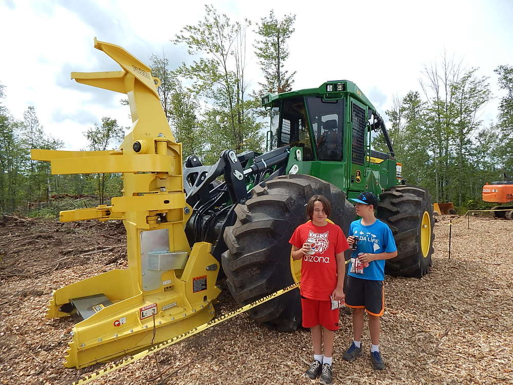 Gabe (L) and Logan Kiel check out a John Deere 843L feller buncher with a tree puller.