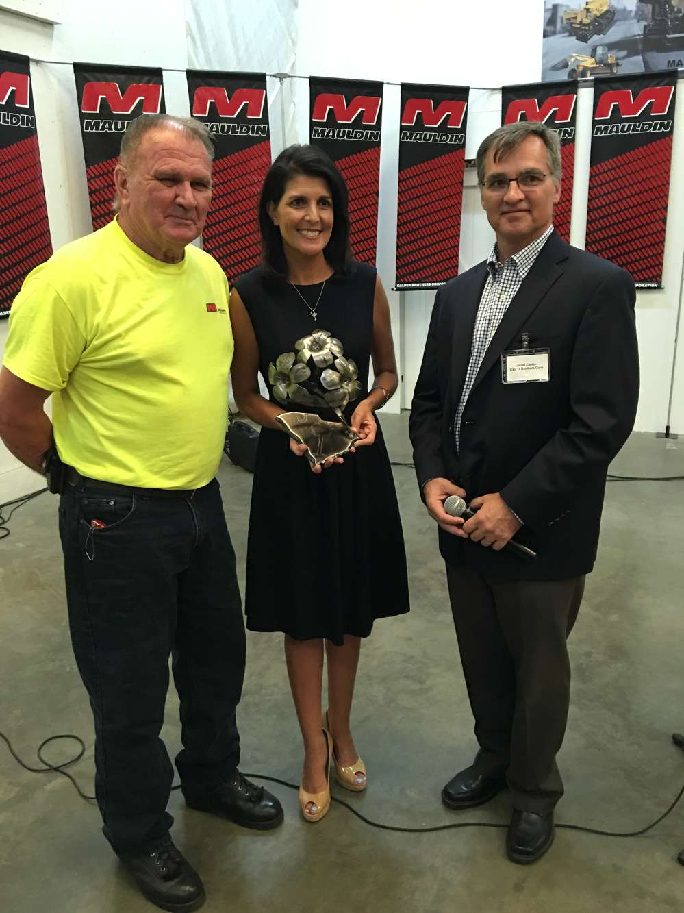 John Craig (L), master welder of Calder Brothers, and David Calder present Gov. Nikki Haley with this one of kind steel welded sculpture of a Yellow Jessamine, South Carolina's state made by Craig on behalf of Calder Brothers.