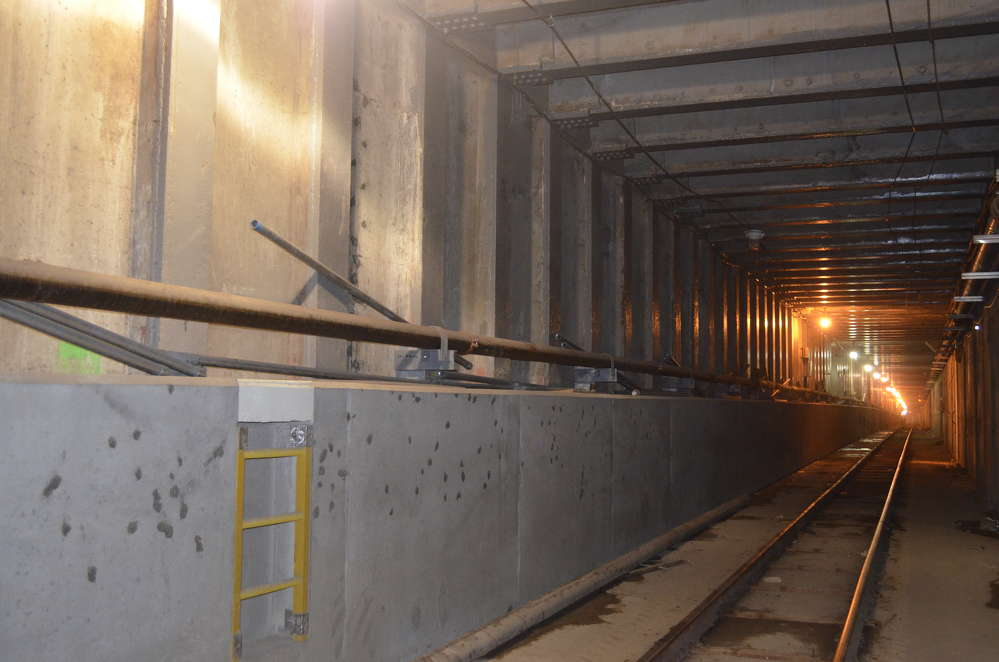 The rehabilitation work being done in this section of the tunnel was initially constructed in the 1970s. The walls and ceiling are square compared to the circular construction in other areas of the tunnel. The left lower side of the photo shows the finished duct benches that were completed by Frontier-Kemper. The concrete protects the utilities contained within it and provides and emergency walkway.