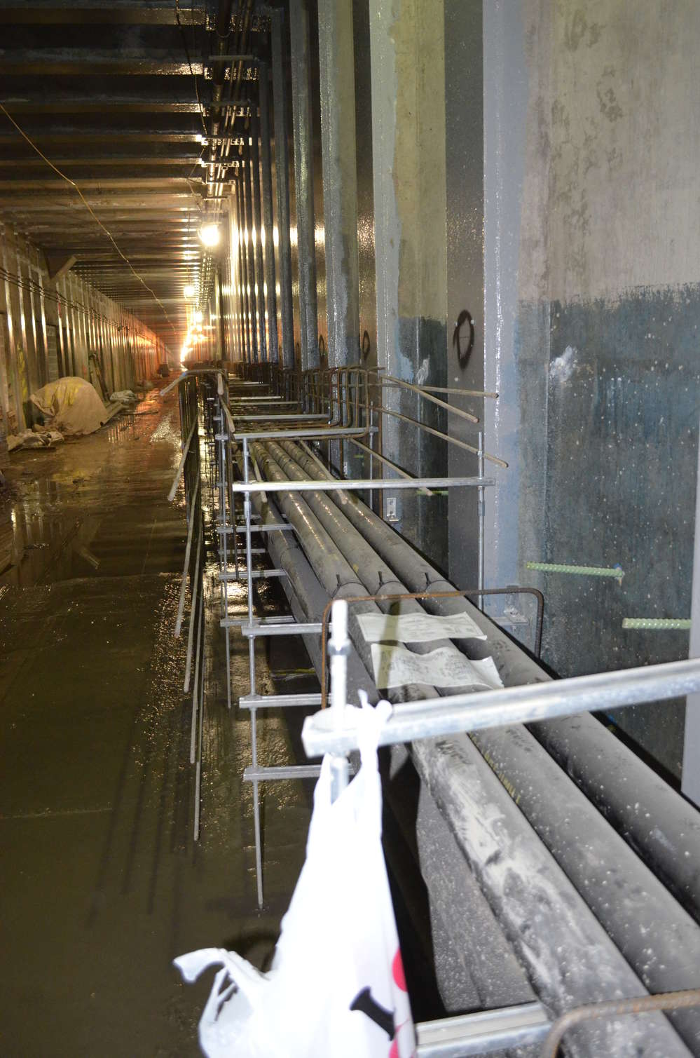 Conduits and reinforcing steel can be seen running along the length of the tunnel before the concrete is placed to create the duct bench.