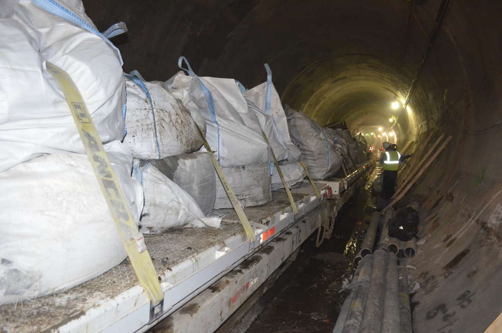 A railcar loaded with bags of debris works its way through a section of the tunnel.