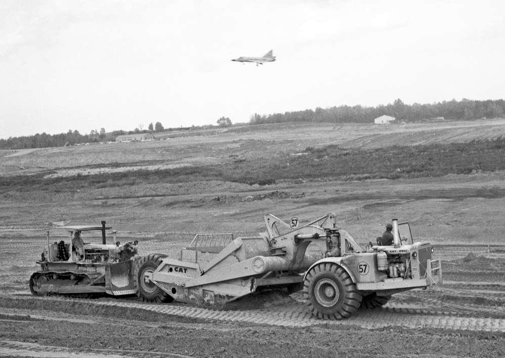 A Caterpillar DW-21 scraper being push loaded with a Caterpillar D8 bulldozer. A fighter jet soars above the AFB.