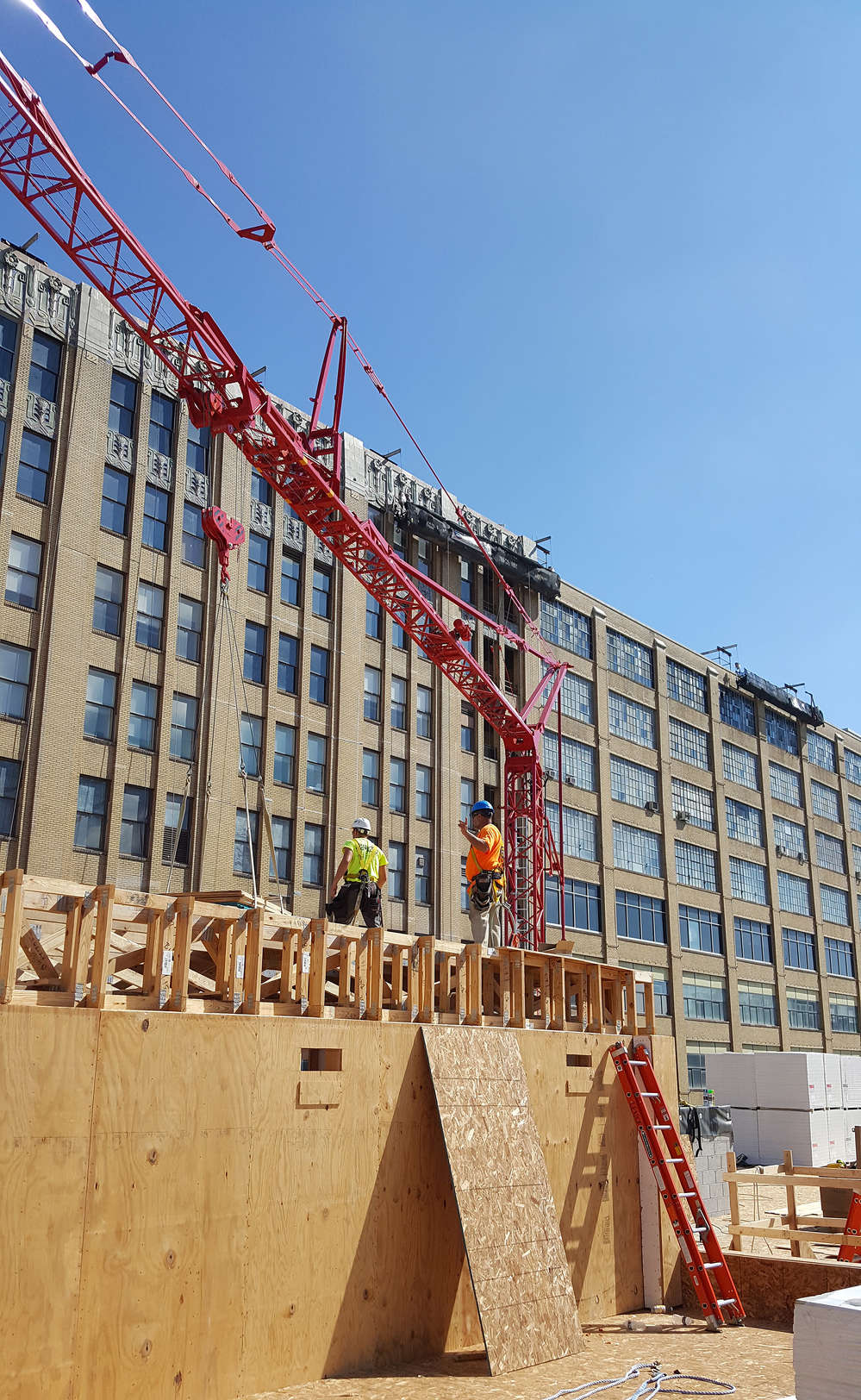 Lenick workers unload roofing materials using Stephenson's Potain T130 tower crane. Using the Potain tower cranes on the Hanover at North Broad Project is projected to save Lenick close to 50 percent in costs and man-hours over using traditional hydraulic cranes.