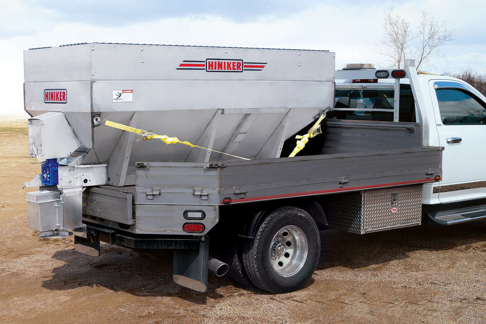 A convenient tip-up spinner assembly makes unloading unused material simple and provides easy trailer hitch access.