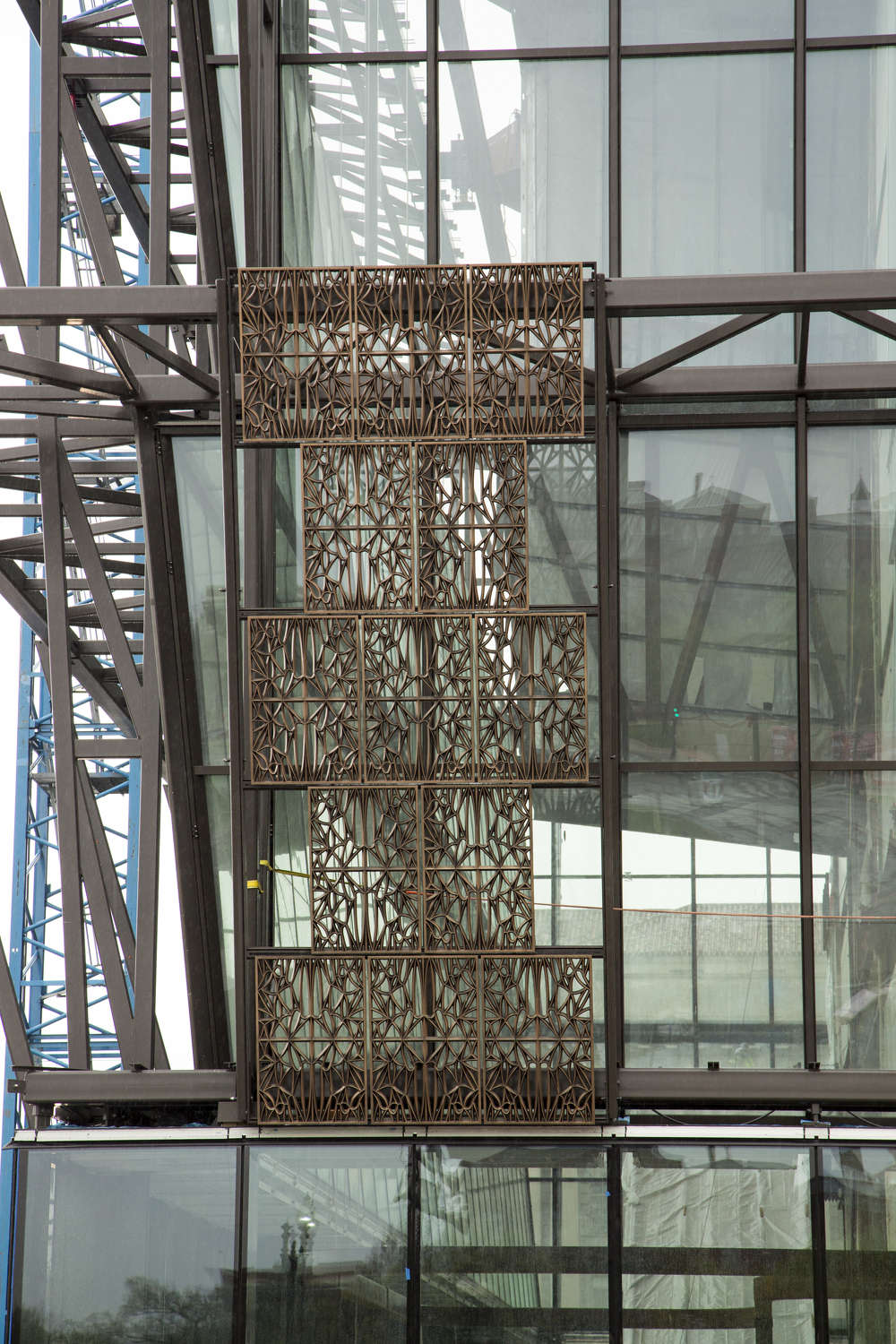 """Michael R. Barnes / Smithsonian Institution photo The first of 3,600 bronze-colored """"Corona"""" panels are installed on April 14, 2015. The """"Corona"""" is the three-tiered structure forming the exterior of the National Museum of African American History and Culture."""