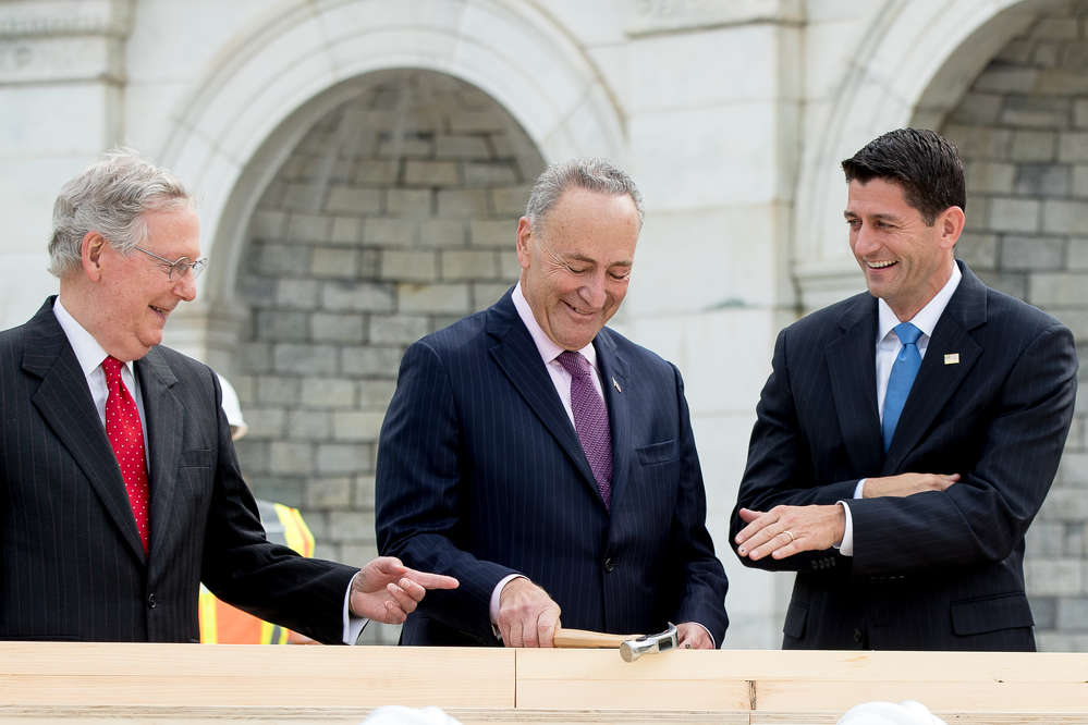 AP Photo/Andrew Harnik). House Speaker Paul Ryan of Wis., right, and Senate Majority Leader Mitch McConnell of Ky., left, laugh at Sen. Charles Schumer, D-N.Y., center, bends his nail during a ceremony to drive in the first nails to signifying the  start of construction on the presidential inauguration platform,