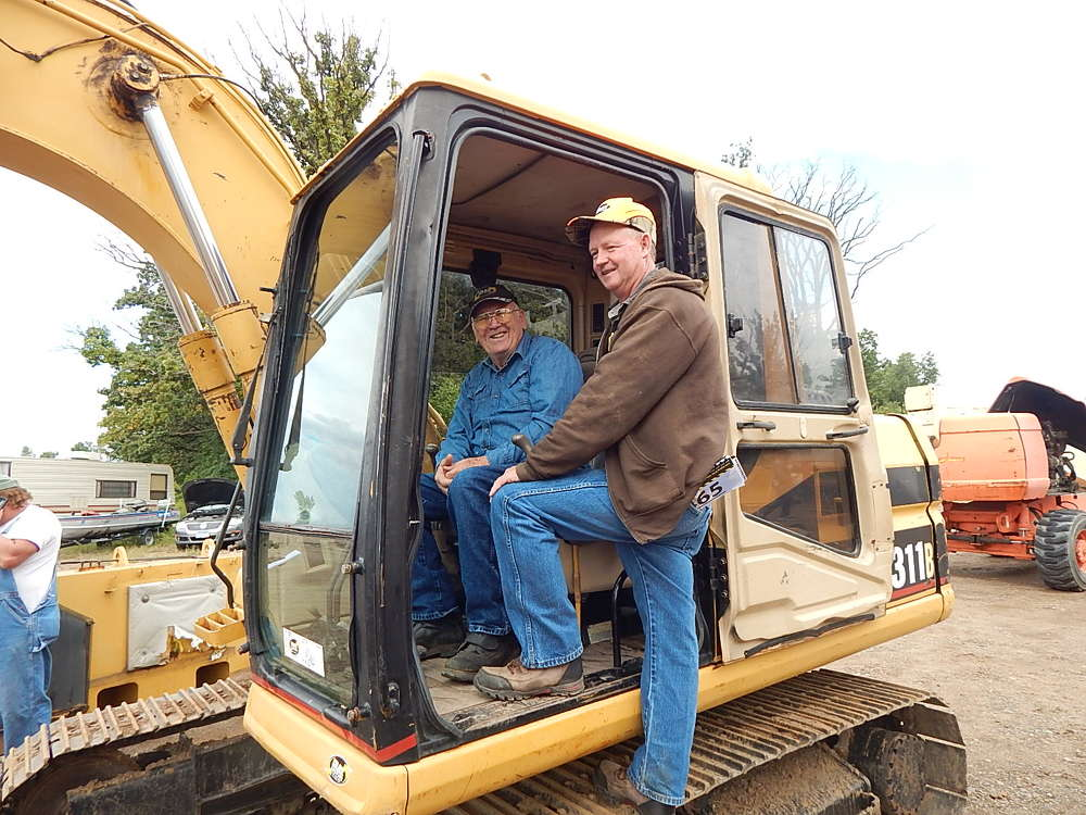 (L-R) Wayne Rambo (L) runs a salvage yard in Wheeler, Wis., and Elmo Eblen works on road maintenance. Both stopped to look at this Cat 311B excavator.