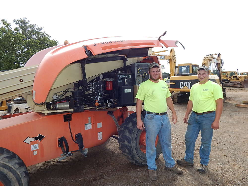 Keith Posch (L), owner of Tri-Country Septic, Hollingsford, Minn., and Tanner Pierskalla, Tri-State, look at this JLG 600S lift.