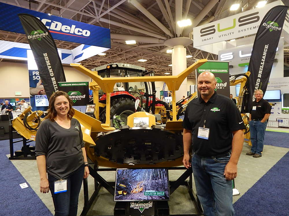 Mel Peterson (L), director of marketing, and Brad Block, regional sales manager, both of Diamond Mowers, answer questions about this Diamond FB5-060 skid steer and  forestry head.