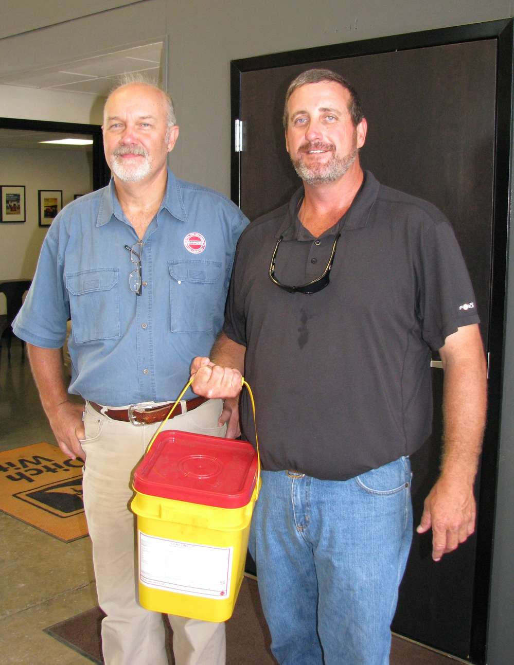 Mark Whittle (L) of Baroid Industrial Drilling Products, Lexington, S.C., provides a sample bucket of Baroid Clay-Drill to his customer Larry Rodgers of HDD Inc., Tallassee, Ala.