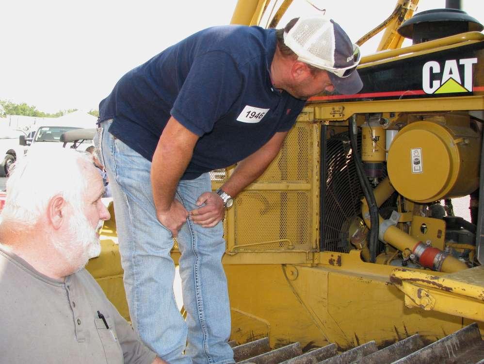 Joe Hibbs (L), Hibbs Grading and Hauling, South Pittsburg, Tenn., and Jon Polk, Landworks Earth Moving, Paducah, Ky., inspect the engine of this Cat D6R.