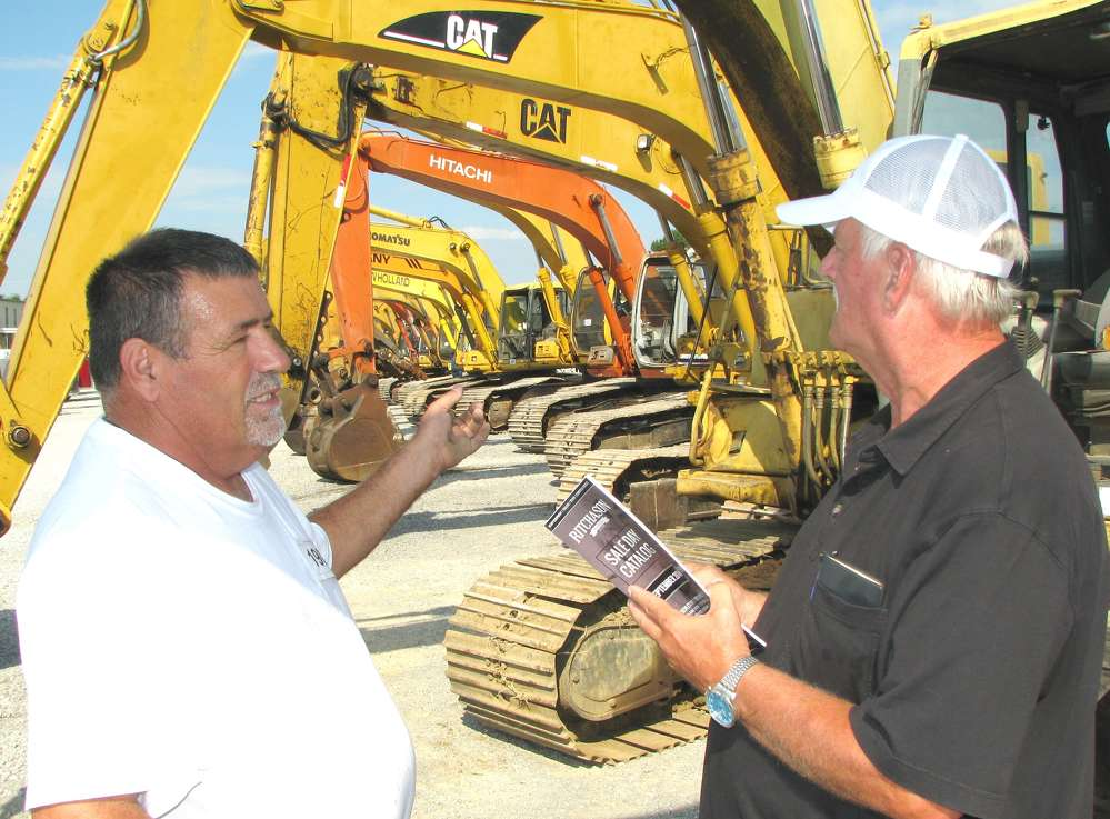 Kenny Bishop (L) and B.Y. Peery, both of Peery Enterprises, Dickson, Tenn., discuss the excavators available at the auction.