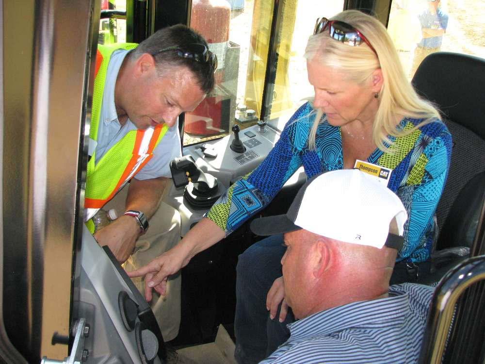 (L-R): Sam Meeker, Caterpillar, goes over all functions displayed on the grade control monitor in the cab of a Cat D6N with Saiia Construction's Connie Hardin and Jay McGinnis.